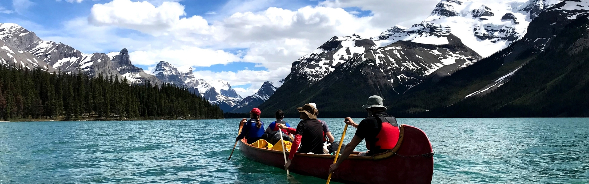 Photo of large red canoe being paddled on lake in the Rocky Mountains.