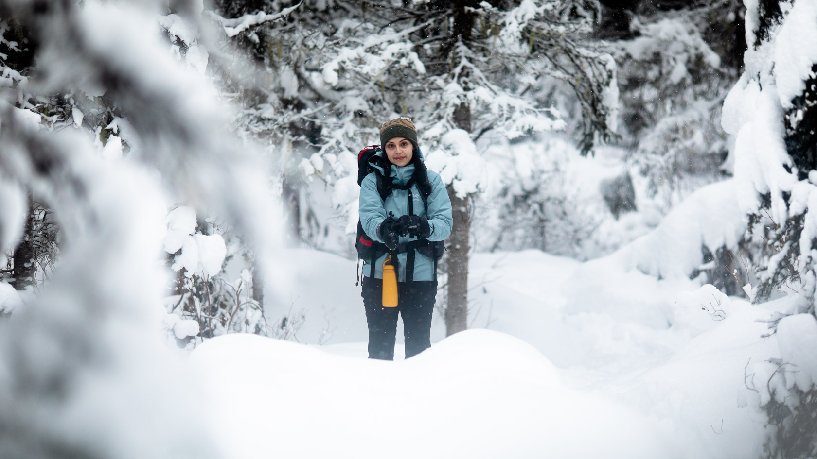 A women fully clad in winter hiking gear, pulls on her mitts while smiling into the camera, surrounded by a winter wonderland.