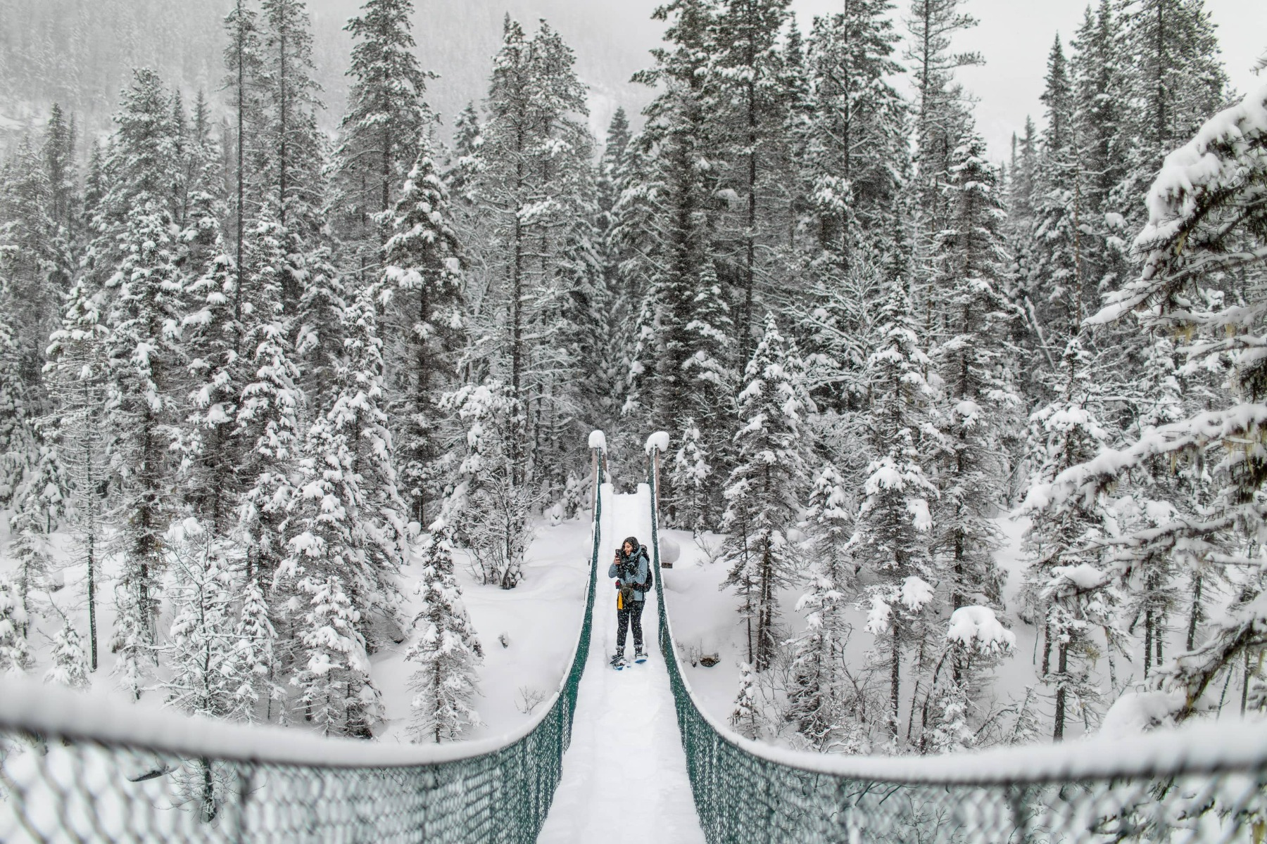 A woman with a hiking pack and snowshoes stands on a long suspension bridge in a snow storm in the mountains.