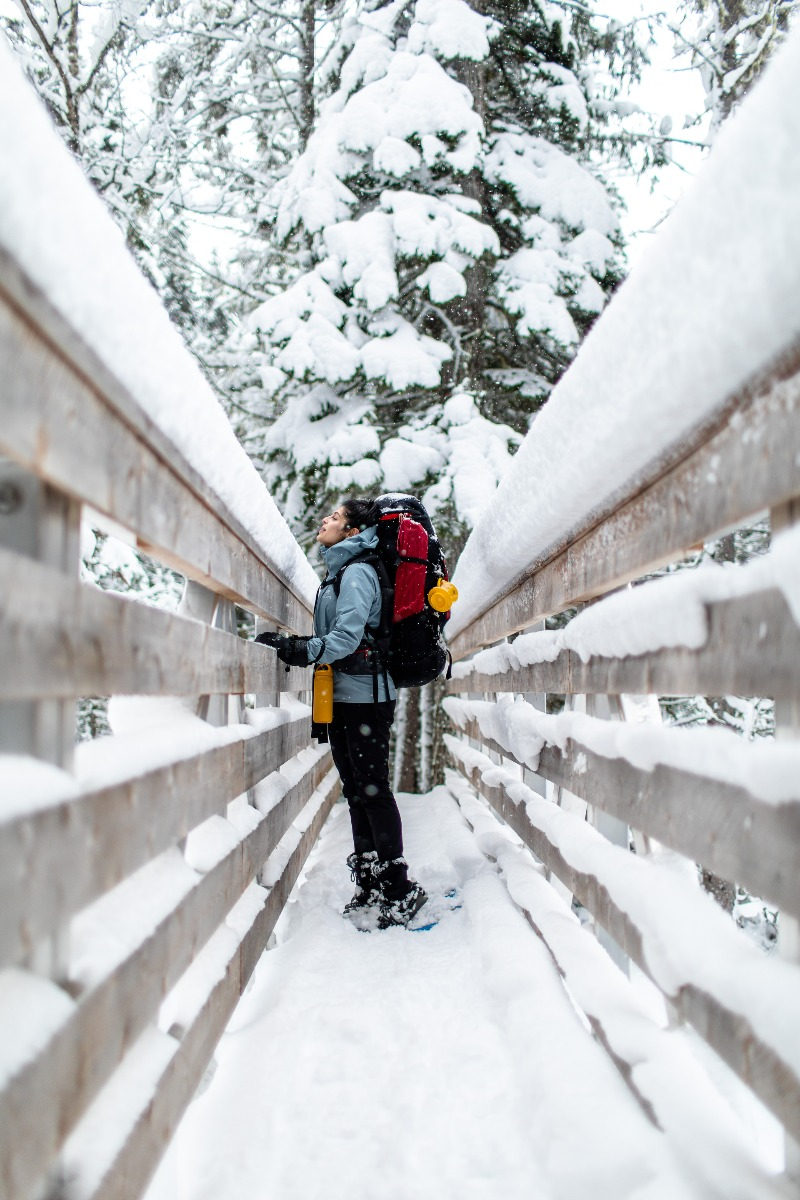 A woman with hiking gear and snowshoes on tries to look over a tall bridge ledge with a foot of snow piled on top.