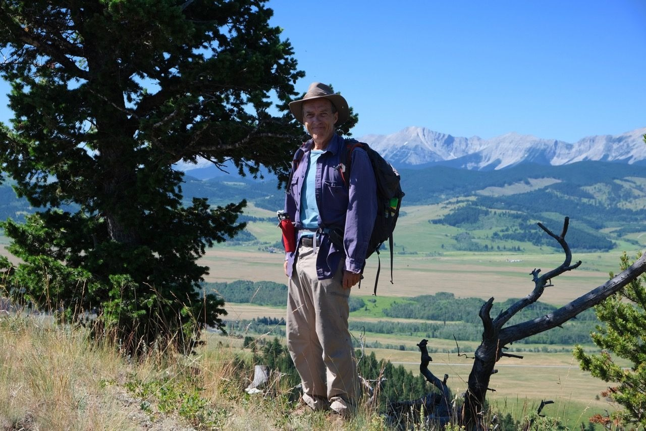Photo of Kevin Van Tighem standing on a trail in the mountains.