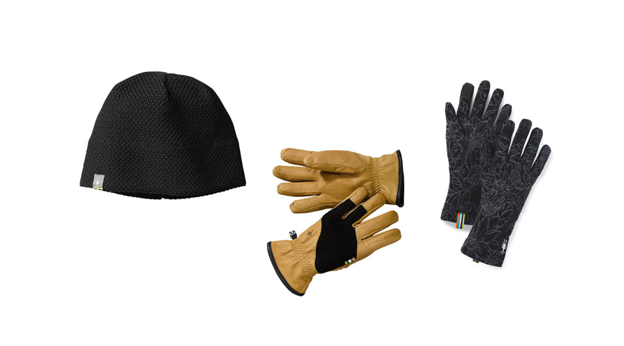 A grey beanie, and two pairs of gloves lay flat on a white background.