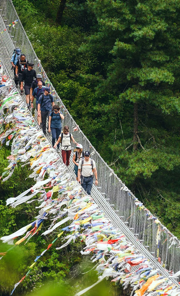 A long line of people hiking across a suspension bridge adorned with mountain prayer flags.