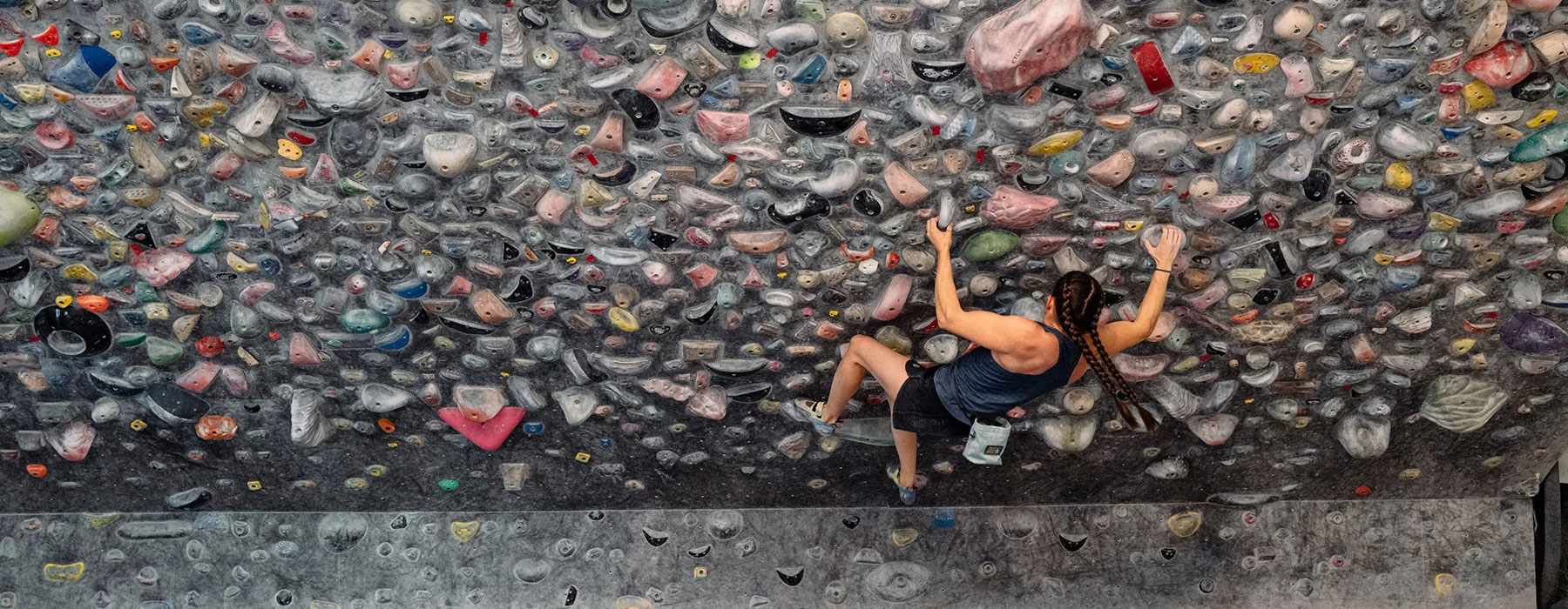 An edge to edge narrow image of a bouldering wall covered in holds and a solo person climbing on the right hand side.