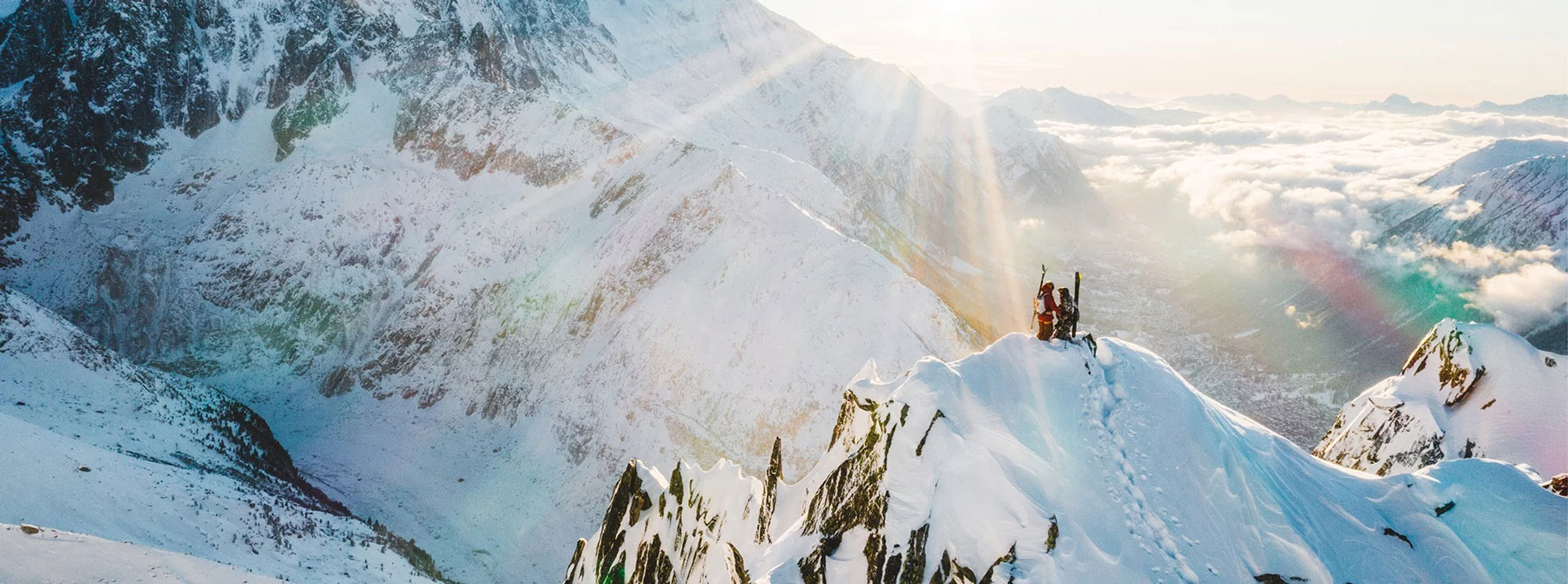 A vast mountainous landscape with two people and ski mountaineering gear on a lone peak in the foreground overlooking endless mountains.