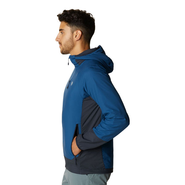 A man wearing the blue Kor Cirrus™ Hybrid Hoody looking to climber left in profile.