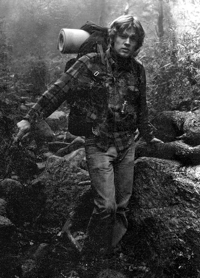 Mike hiking through a forrest wearing a pack with sleeping roll tucked into the top, a black and white photo that feels old.